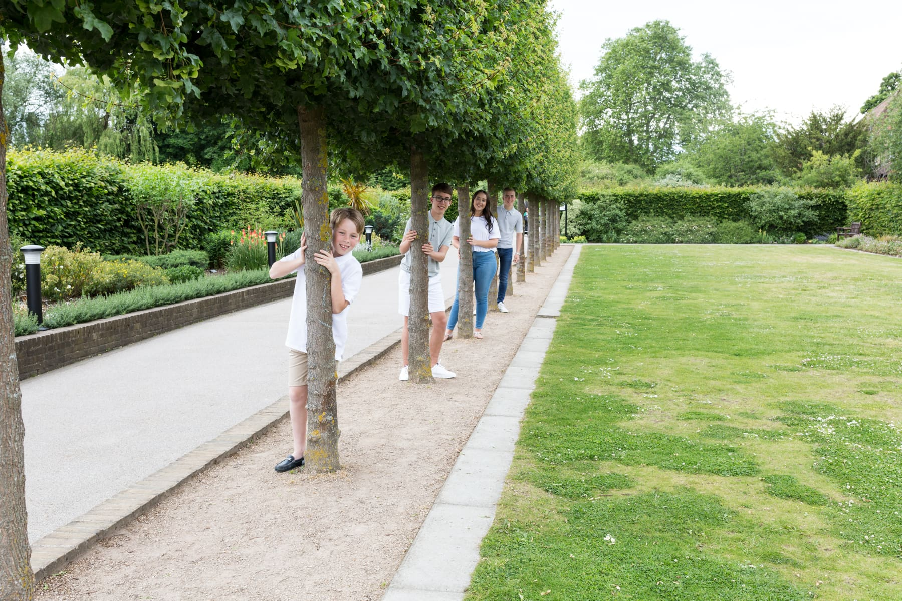 siblings standing in a line of trees at their Bexley family photoshoot