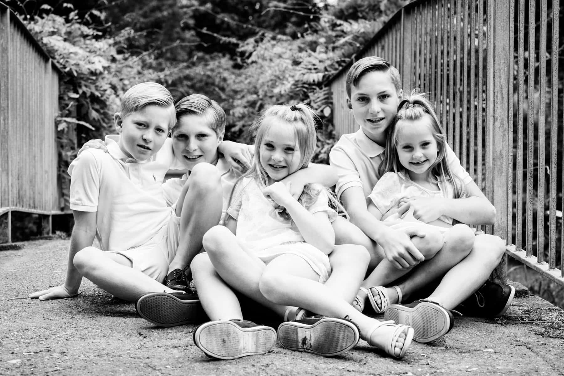 siblings sat on floor on bridge at their family photoshoot in Bexley