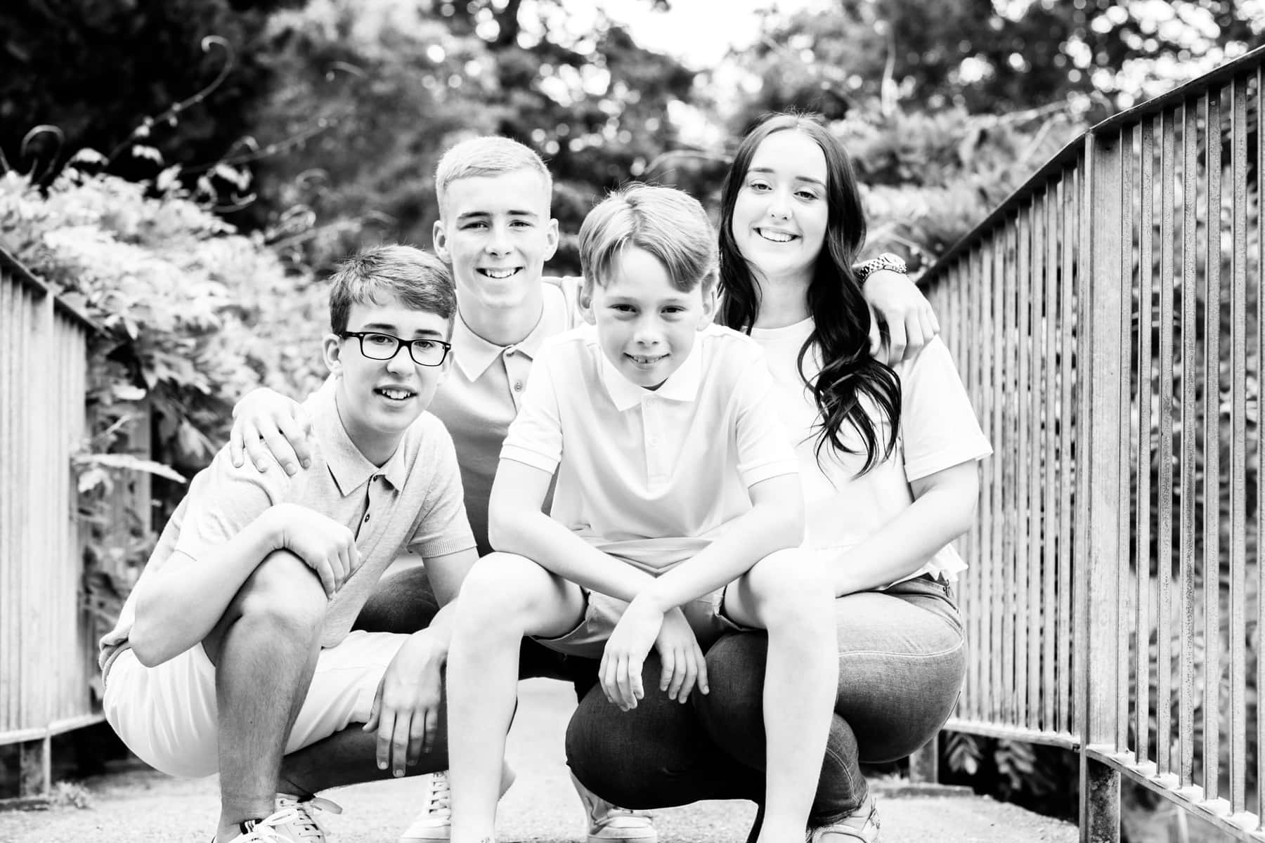siblings crouched down on a bridge at their Bexley family photoshoot