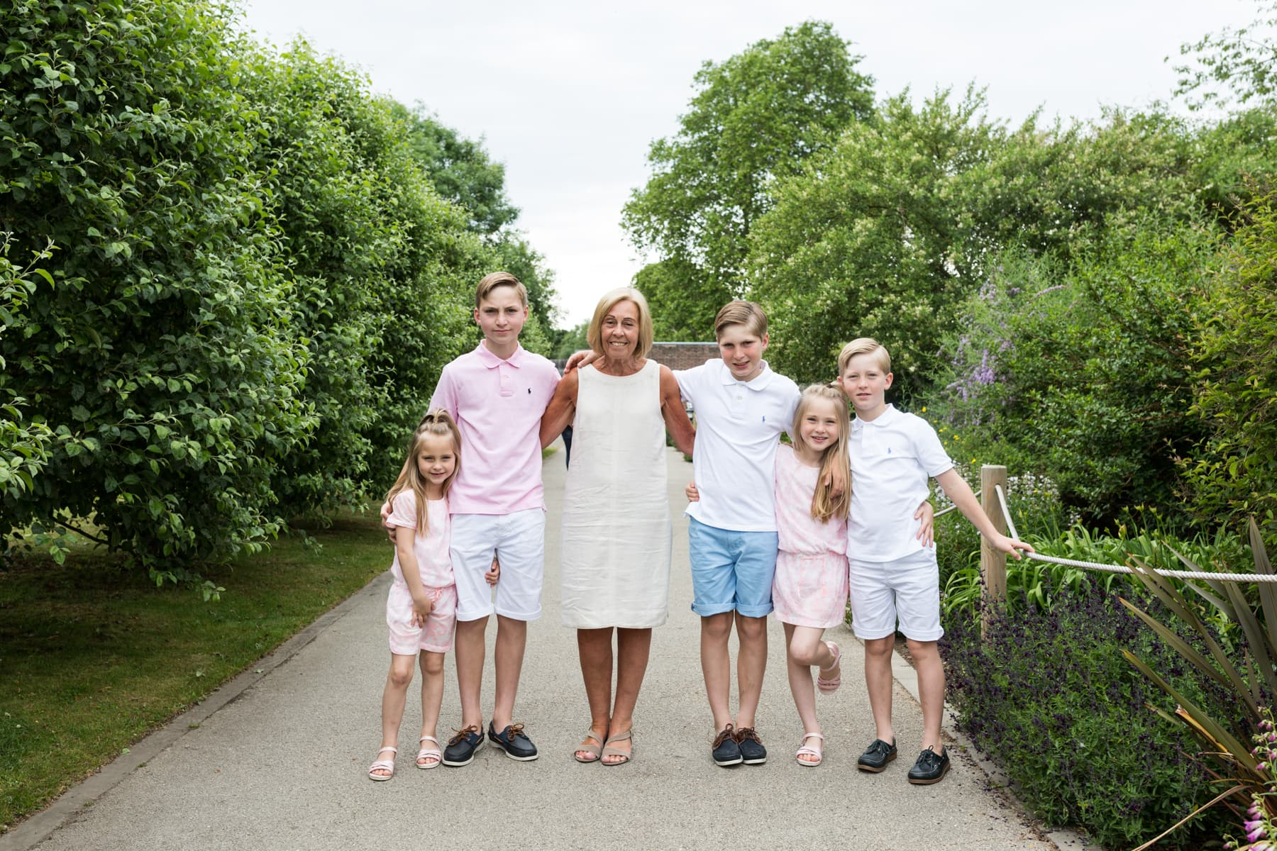 Nana and 4 grandchildren standing between trees at their Bexley extended family photoshoot