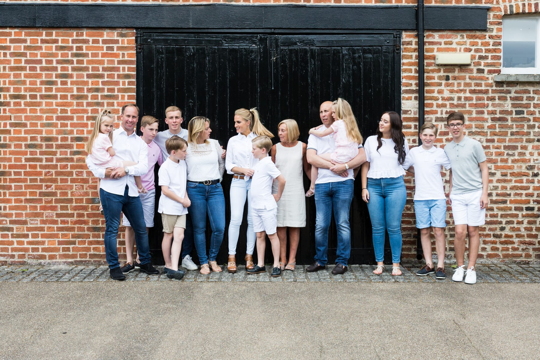 extended family casual shot chatting standing in front of black barn doors at their Bexley extended family photoshoot