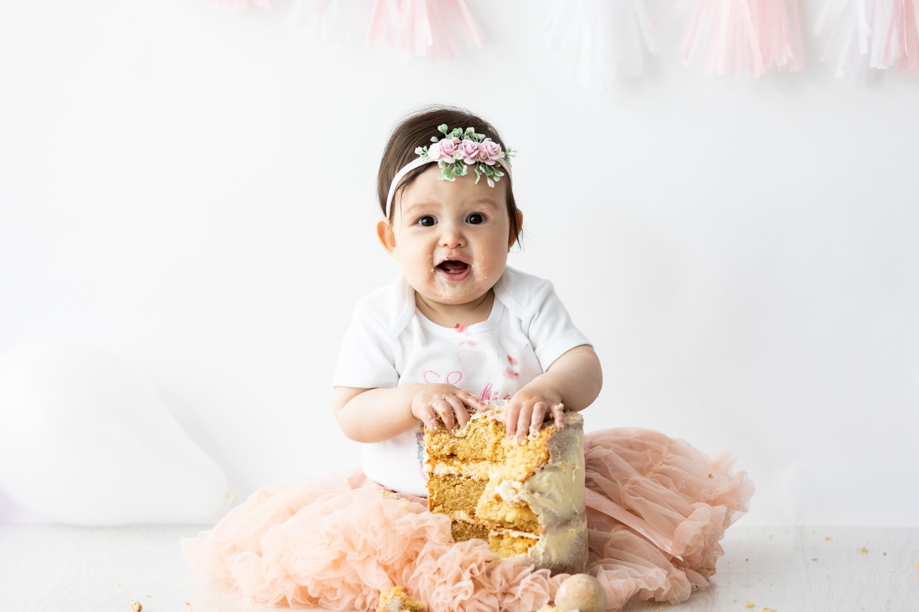 little girl with cake in her lap wearing tutu from our kid at her natural set up Kent cake smash shoot