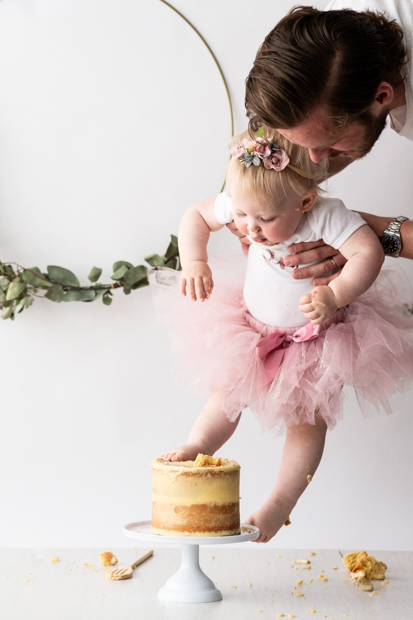 baby girl in daddy's arms with feet in her cake at her Kent cake smash photoshoot in Bexley