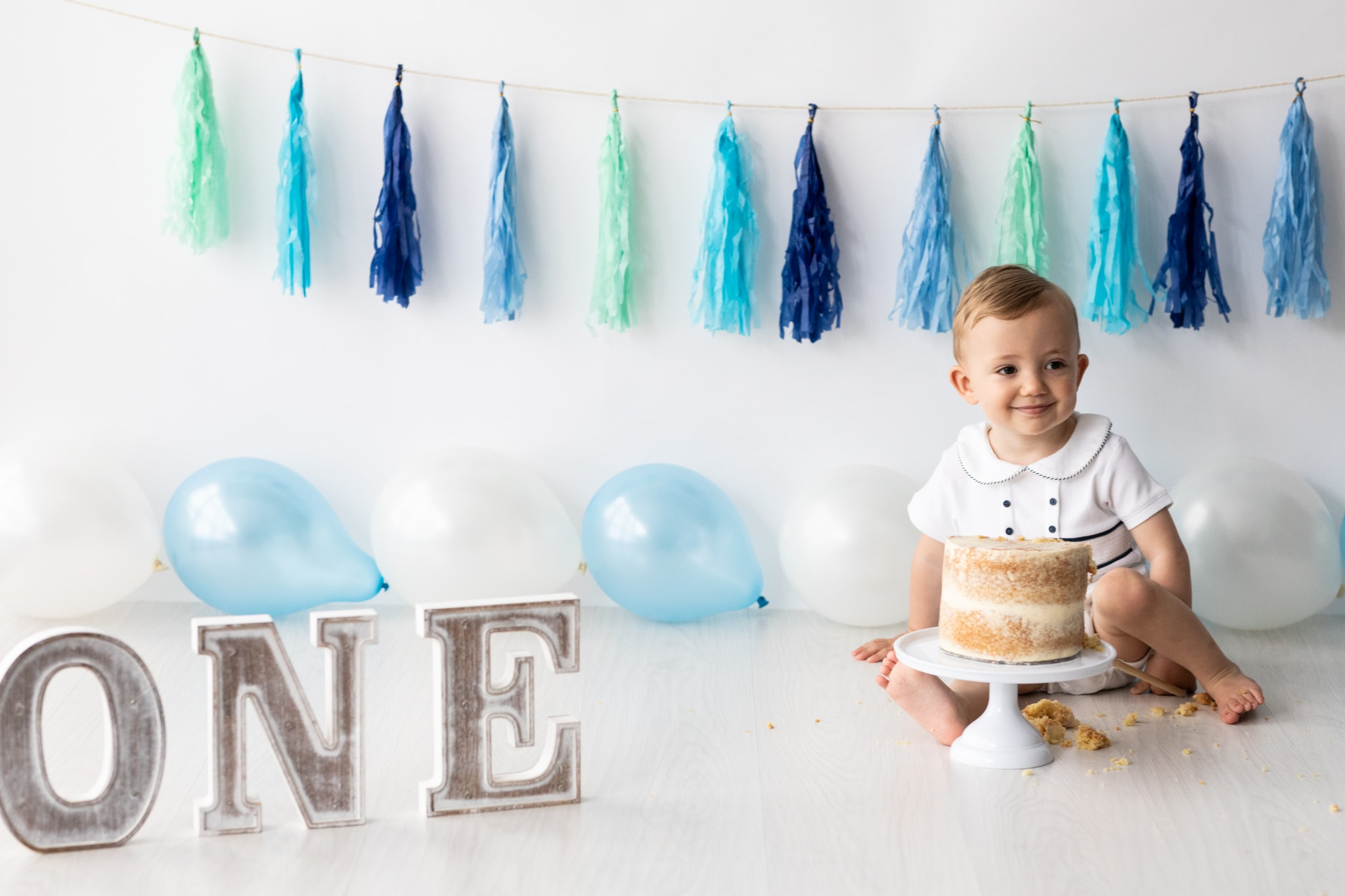 little boy at his Kent cake smash photoshoot with a neutral set up