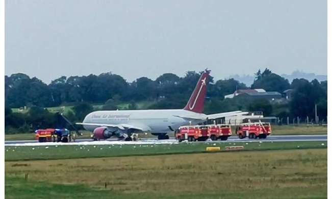 Firecrews attend an Omni Air International aircraft on the tarmac at Shannon Airport in County Clare, western Ireland, after  a