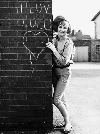 lulu-pop-singer-stands-besides-wall-in-1964