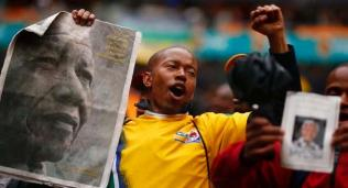 People start singing as they arrive for a mass memorial for Nelson Mandela in Johannesburg