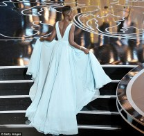 Lupita lifts her Prada gown to make sure she doesn't trip on her way to the stage