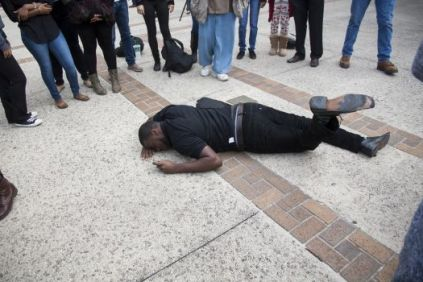 UTSA senior Chris Brown initiates the event by falling first to the ground Wednesday Dec. 10, 2014 during a Die-in in honor of Michael Brown and Eric Garner