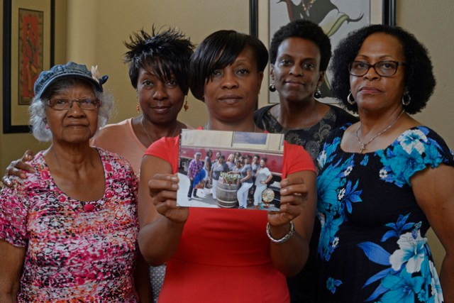 Five members of the Sistahs on the Reading Edge book club, all of Antioch, from left, Katherine Neal, Georgia Lewis, Lisa Renee Johnson, Allisa Carr and Sandra Jamerson stand together at Johnson's home in Antioch, Calif., on Monday, Aug. 24, 2015. The five women were among 11 African-American women who were were booted off the Napa Valley Wine Train on Saturday afternoon. Johnson holds a photograph of the group that was taken before boarding the train. (Jose Carlos Fajardo/Bay Area News Group)