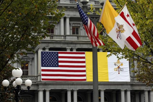 An American flag, the Vatican City, and city of Washington flags are seen in front of the Eisenhower Executive Office Building on the White House complex in Washington, Tuesday, Sept. 22, 2015, in preparation for the upcoming visit by Pope Francis. (AP Photo/Alex Brandon)