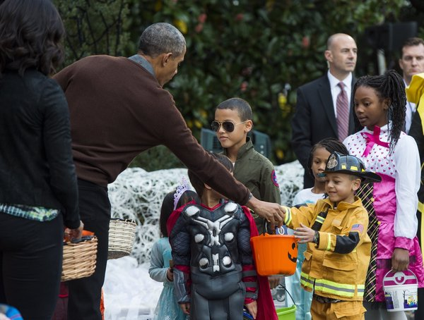 US President Barack Obama and First Lady Michelle Obama hand out treats to children trick-or-treating for Halloween on the South Lawn of the White House in Washington, DC, October 30, 2015. AFP PHOTO / SAUL LOEB        (Photo credit should read SAUL LOEB/AFP/Getty Images)