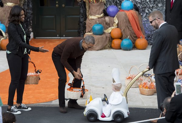 """US President Barack Obama and First Lady Michelle Obama greet a young child dressed as the Pope and riding in a """"Popemobile"""" as he hands out treats to children trick-or-treating for Halloween on the South Lawn of the White House in Washington, DC, October 30, 2015. AFP PHOTO / SAUL LOEB        (Photo credit should read SAUL LOEB/AFP/Getty Images)"""