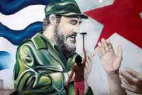 A child plays in front of a mural of late former Cuban leader Fidel Castro in Managua