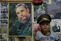 Marlon Mendez (10), who claims to be an admirer of Cuba's former president Fidel Castro, poses inside his bedroom that is adorned with pictures of Castro, in Artemisa province, Cuba