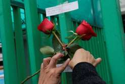 A woman places flowers on a fence as part of a tribute following the announcement of the death of Cuban revolutionary leader Fidel Castro, outside the Cuban Embassy in Mexico City