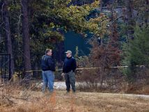 Law enforcement personnel stand near police tape on Todd Kohlhepps property in Woodruff