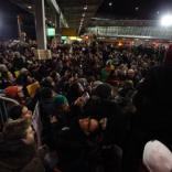 """Protester holds a cardboard sign reading""""No Ban, No Wall, Sanctuary for All"""" during a rally outside Terminal 4 of Kennedy Airport in Queens, New York, Saturday night following the start of implementation of President Trump's ban on travel to the U.S.A. from certain Muslim countries."""