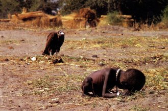 The vulture and the little girl, 1993. Original title: Struggling Girl. The vulture is waiting for the girl to die and to eat her. The photograph was taken by South African photojournalist, Kevin Carter, while on assignment to Sudan. He took his own life a couple of month later due to depression.