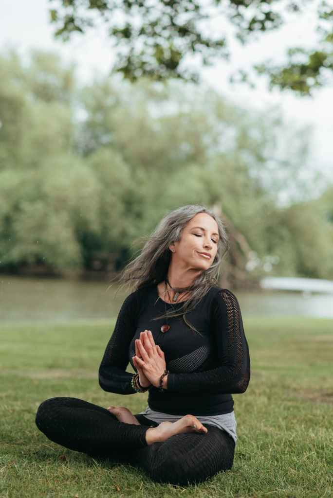 reflective woman meditating in lotus pose with namaste hands