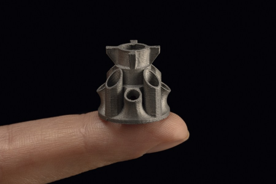A complex metal part the size of a fingertip 3D printed on the Studio System+. Photo via Desktop Metal.