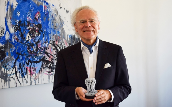 Dr. Hans Langer, founder of EOS, and the 2019 3D Printing Industry trophy forOutstanding Contribution to 3D Printing. Photo via EOS