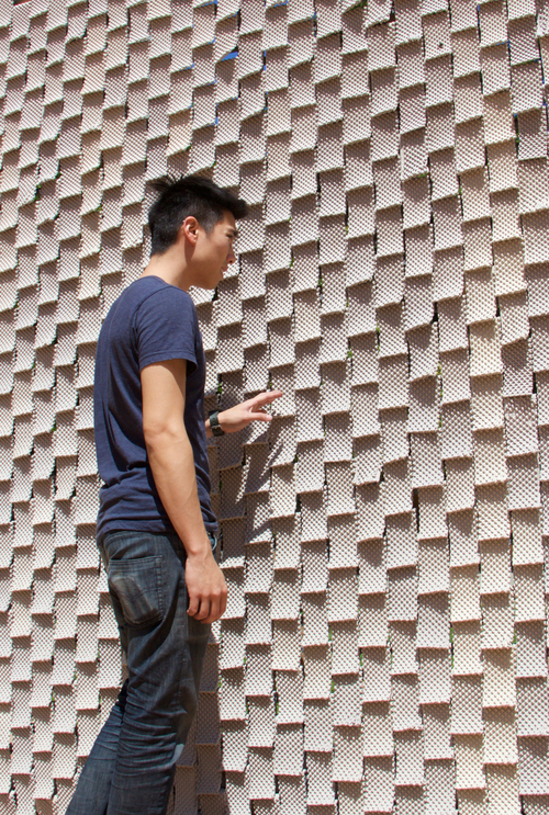 A young man engaging with a wall of 3D printed ceramics