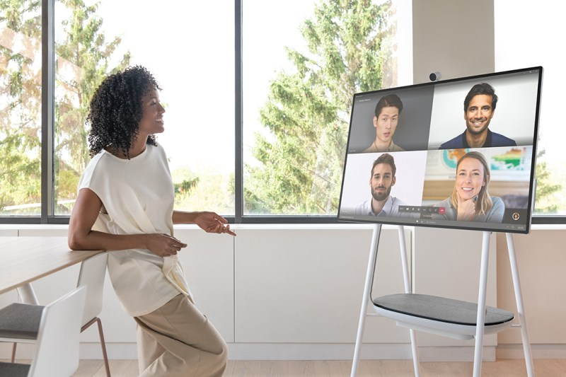 A woman in an office holds a conference call with other team members via Surface Hub 2S