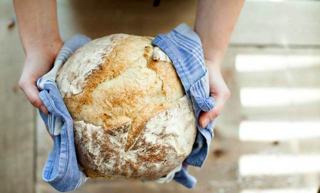 Person holding baked bread covered with towel   Your Road Map To Self Sufficiency