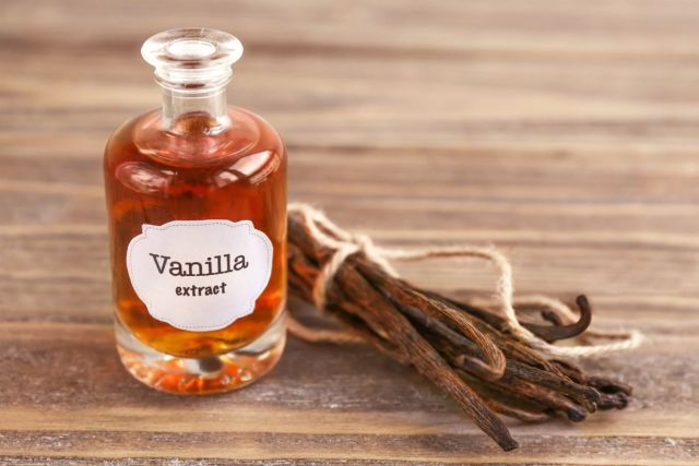 Bottle with aromatic extract and dry vanilla beans on table   Survival Food Items That Will Outlast The Apocalypse