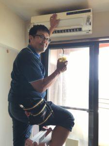 外れた室内機を支えつつ、お客様からいただいたお茶を片手に。エアコンクリーニングの武田快適工房さん