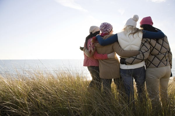 four women hugging by the water
