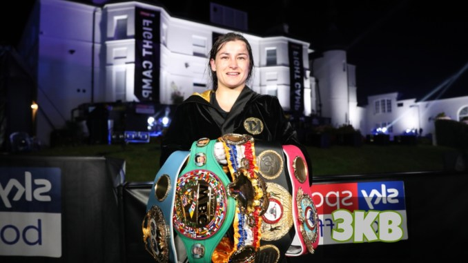 Katie Taylor shows off the WBA, IBF, WBC and WBO belts.