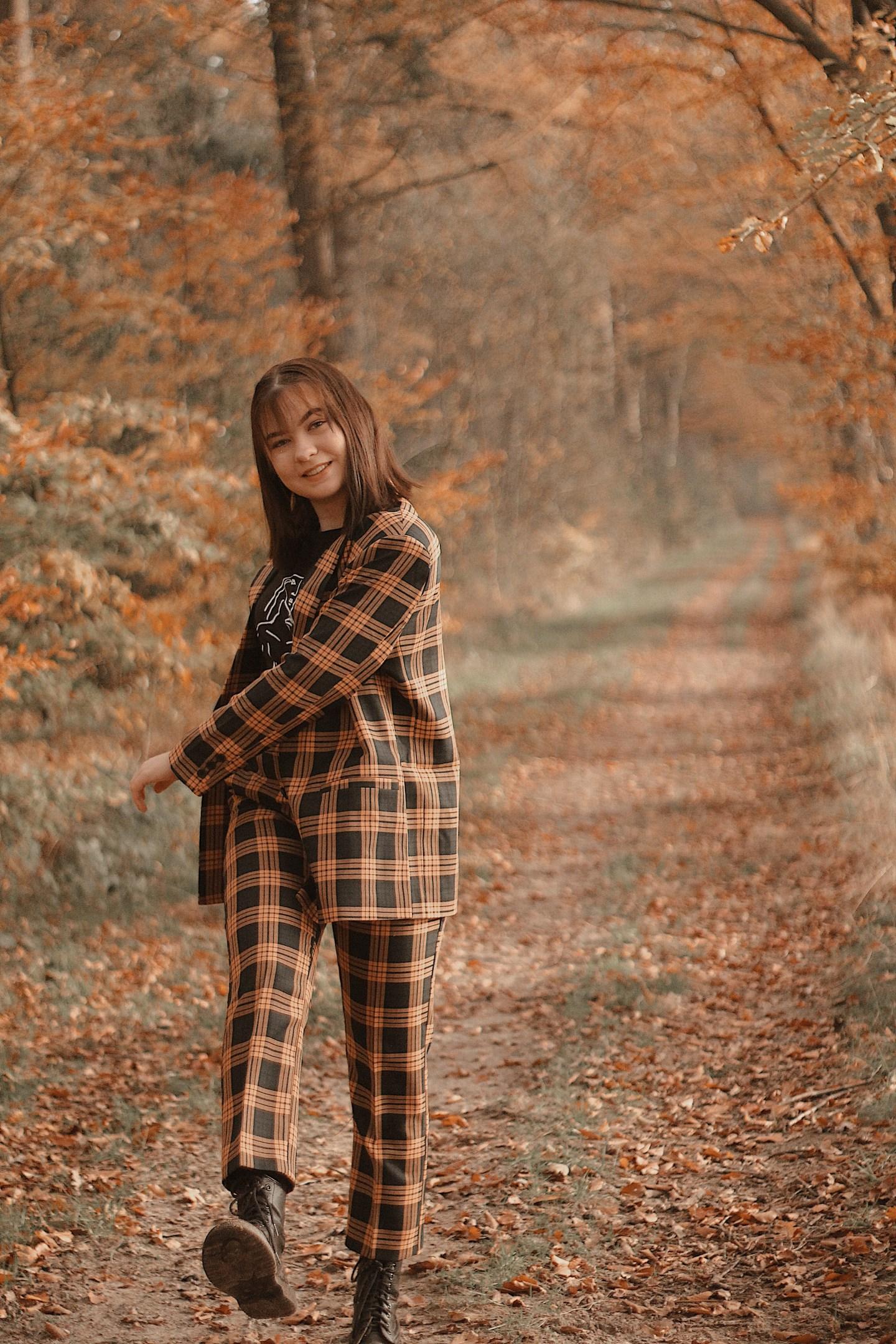 Suit: lachend meisje met tweedelig pak aan in bos en schopt blaadjes weg