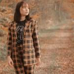 Suit: Foto met meisje met tweedelig pak aan in het bos en ze kijkt weg