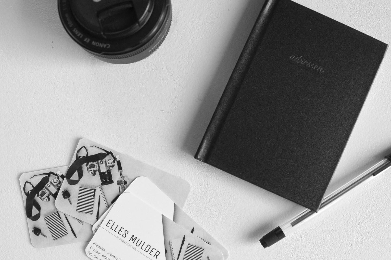 Freelancen: flatlay foto van visitekaartjes, een pen en een notitieboek