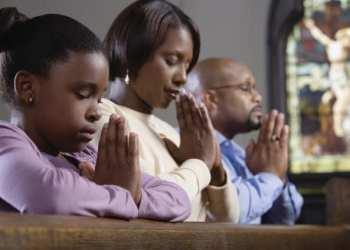 Family praying in church --- Image by © Ocean/Corbis