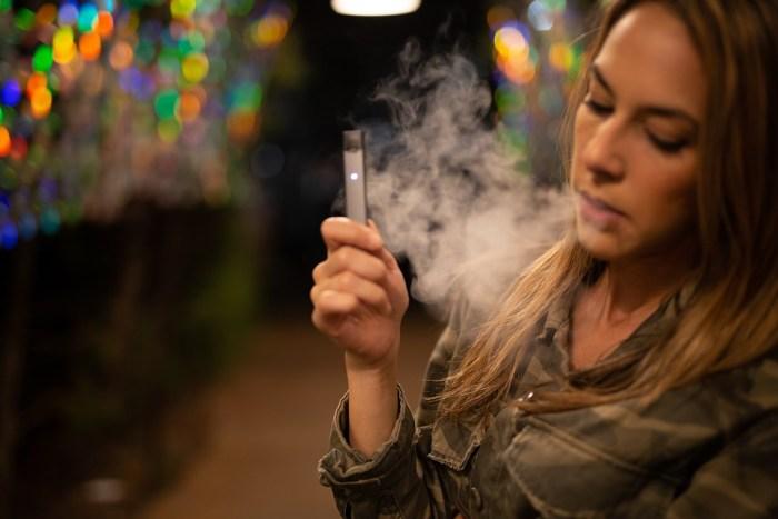 Дівчина курить електронну сигарету