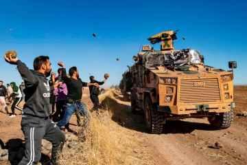 Курди кидають каміння у військову машину