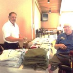 Quartermaster Rick Barzen display Marine apprel to Jim Hughes