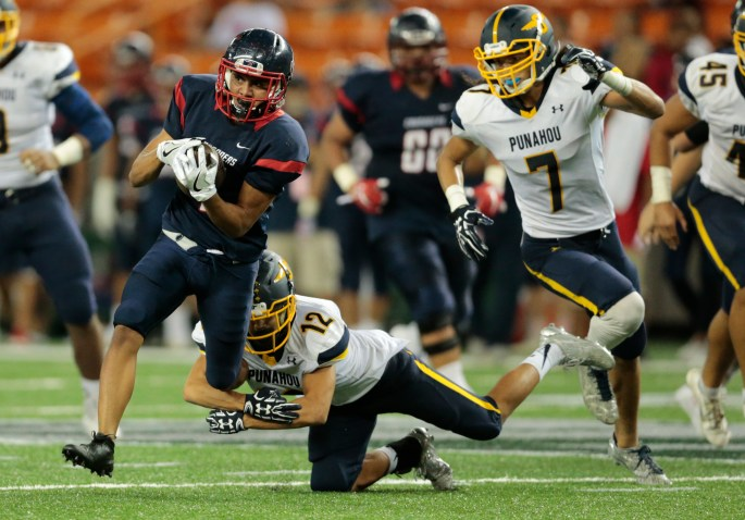 JAMM AQUINO / JAQUINO@STARADVERTISER.COM Saint Louis slotback Tosh Kekahuna-Kalawe (4) tries to elude Punahou defensive back Aaron Woo (12) and defensive back Marist Liufau (7)  during the second half.