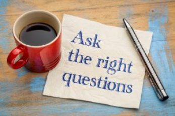 Ask the right questions - handwriting on a napkin with a cup of espresso coffee