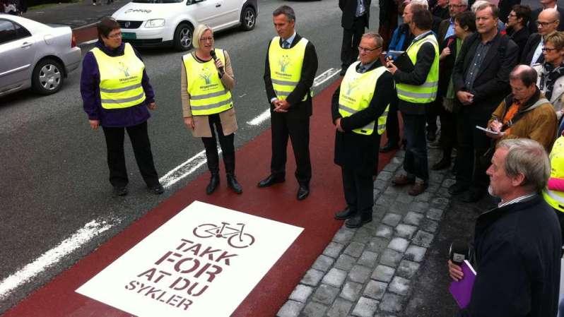 Marit Arnstad og Jens Stoltenberg sprayet inn symbolet for miljøpakken og teksten «takk for at du sykler» i sykkelfeltet ved Gamle bybro i Kjøpmannsgata. Foto: KIM NYGÅRD, ADRESSA