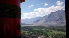 A prayer wheel at the Diskit monastery with the Nubra valley in the background