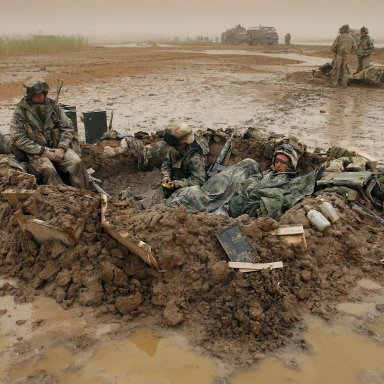 (FILES) -- US Marines from the 2nd batallion, 8th Marine wake up in a mud field after heavy sand storms early in the morning 26 March 2003 in Nasiriyah, about 300kms south of Baghdad. Americans have conflicting views about the costs and benefits of the US-led war on Iraq nearly two years after its launch, according to a poll released 15 March 2005. AFP PHOTO/ERIC FEFERBERG