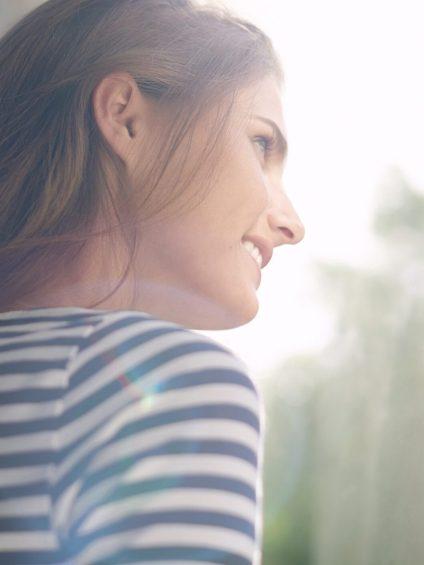 Une jeune femme regarde par la fenêtre et profite des rayons du soleil.