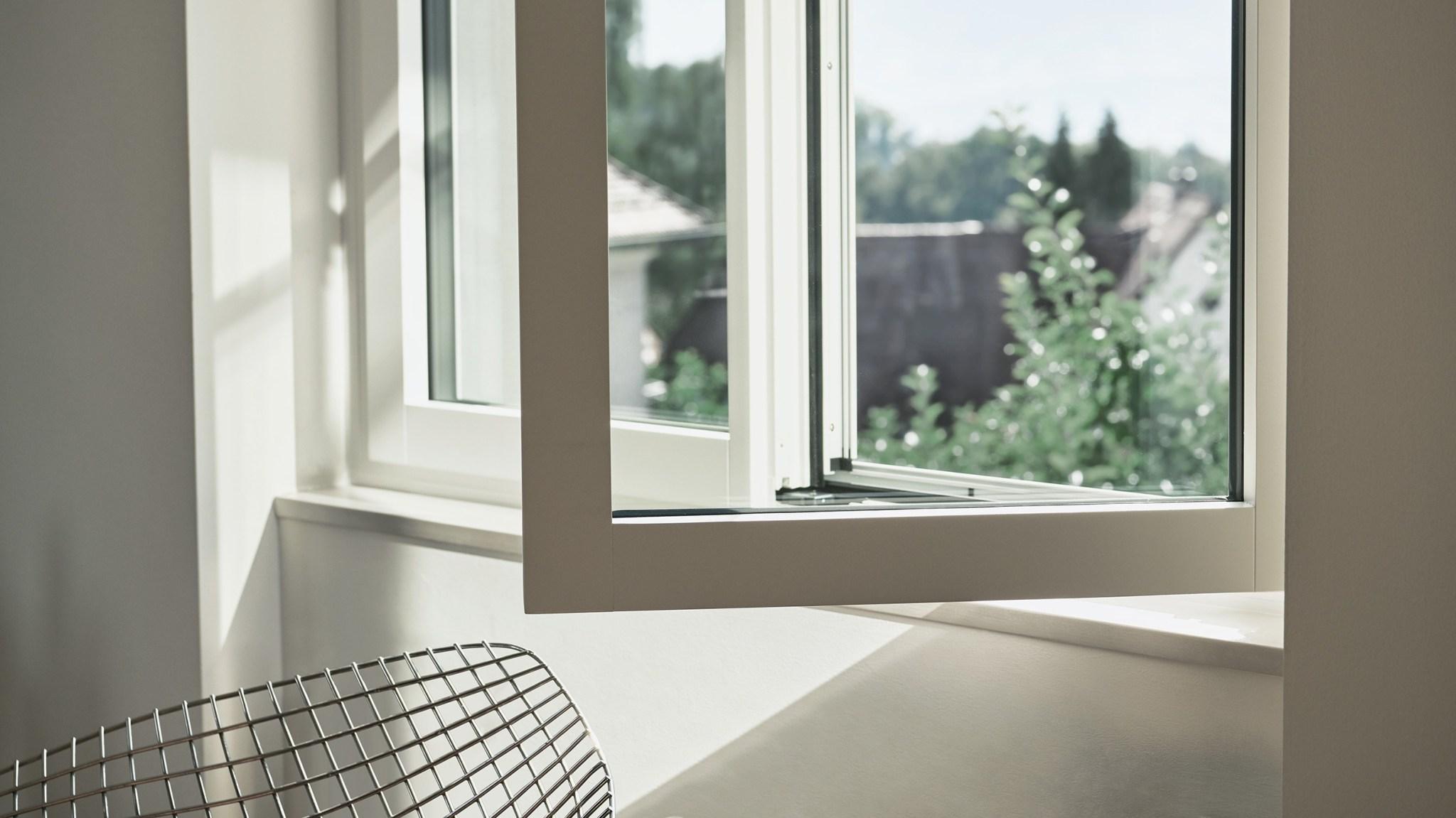 Renovationsfenster RF1 in weiss mit offenem Fensterflügel und Aussicht ins Grüne