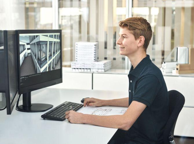 Lernender Arbeitet an Plänen am Computer für den Fassadenbau