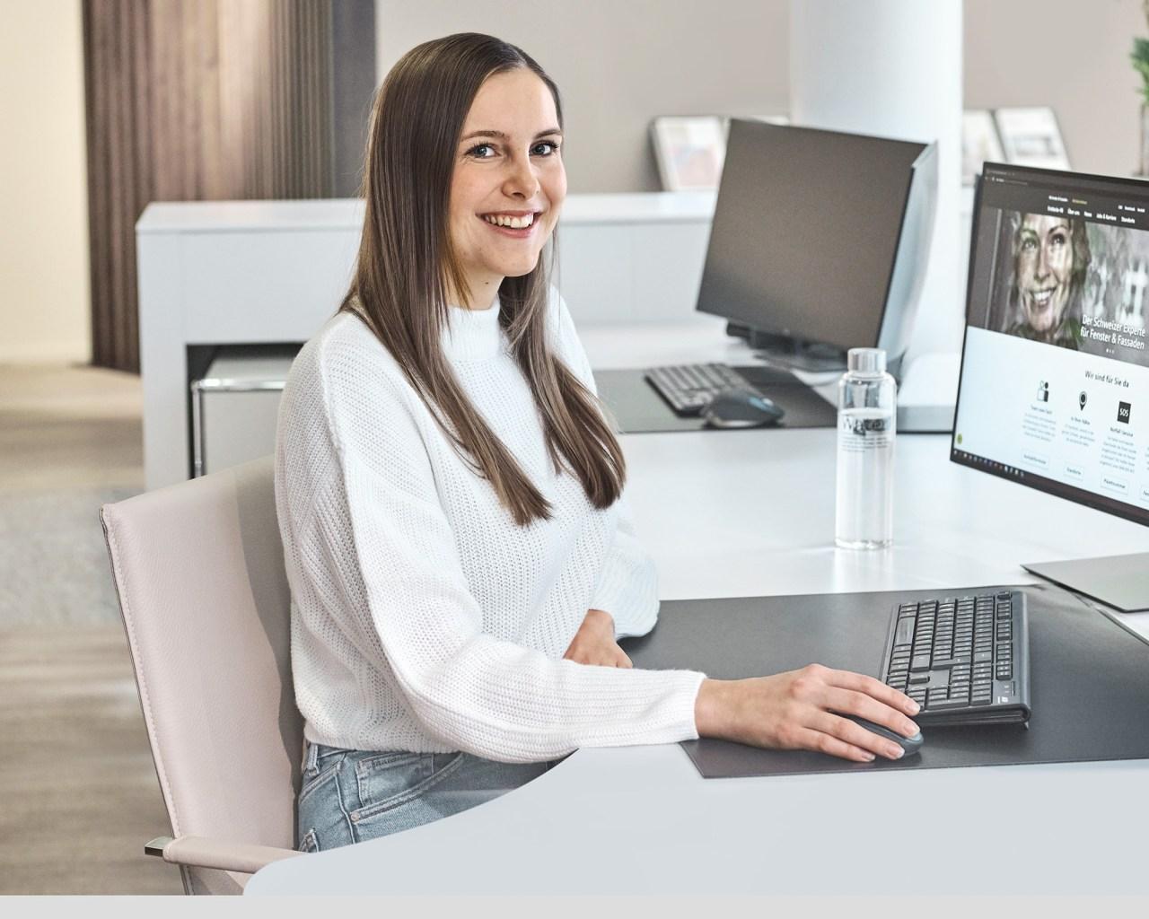 Auszubildende Kauffrau sitzt vor Computer am 4B Empfang