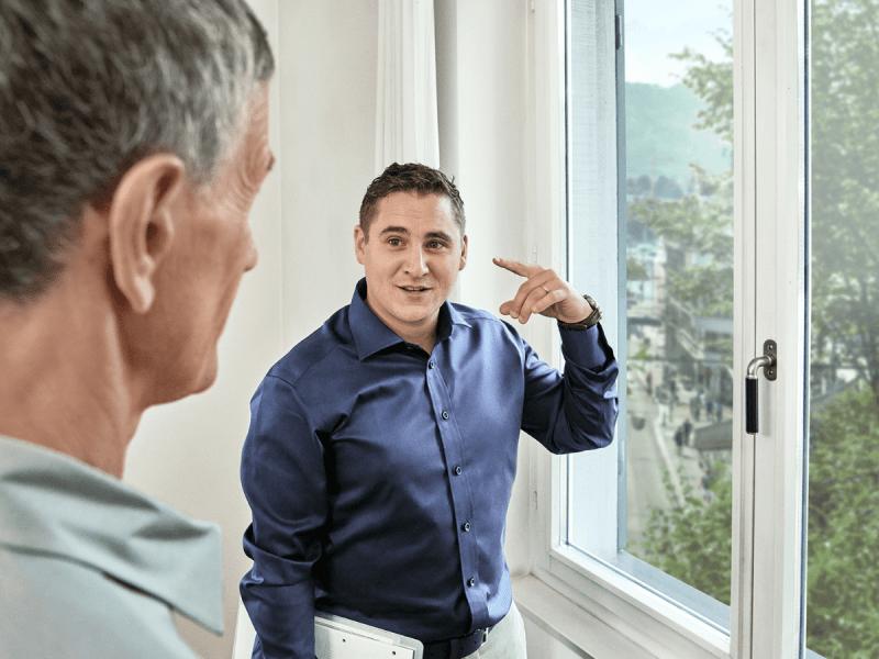 Berater zeigt den Kunden, wie der Schallschutz am Fenster verbessert werden kann